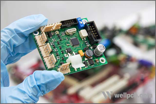 Hand in a blue glove holds PCB chip assembly on PCB background on the production of printed circuit boards.jpg